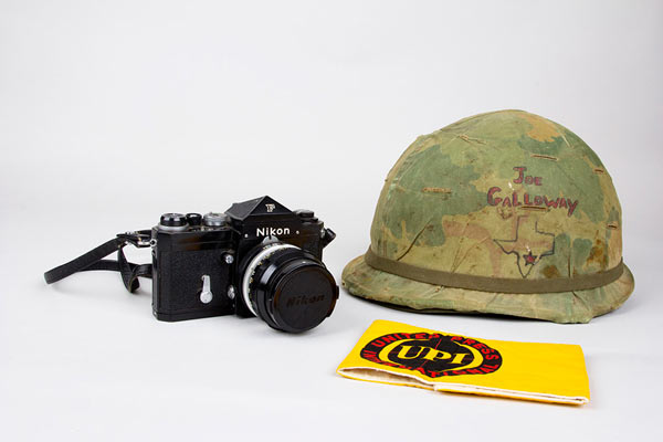 """United Press International reporter Joe Galloway used this Nikon camera throughout his time in Vietnam. He was given this helmet by an Army colonel who noticed him wearing a beret during battle. Galloway said he wore this armband in Saigon so police would know he was a journalist """"when they were beating people on the head."""" (Photo: Amy Joseph/Newseum; Camera, helmet and armband: Loan, Joseph L. Galloway)"""
