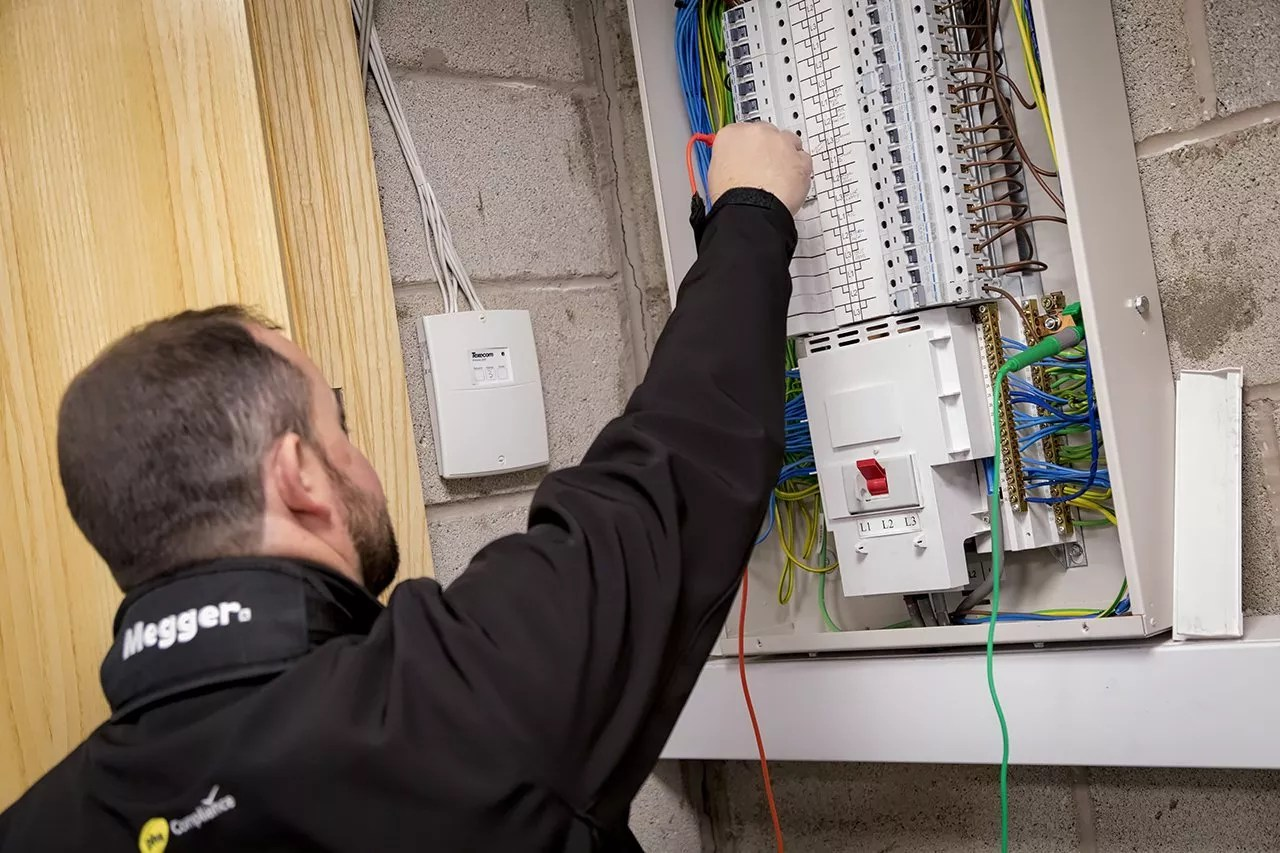 hight resolution of engineer testing distribution board as part of electrical installation inspection fixed wire by phs