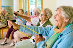 Large group of happy enthusiastic elderly ladies exercising in a gym sitting in chairs doing stretching exercises with rubber bands. Older people, circuit training, arm, hand, smile, rehabilitation, inpatient.