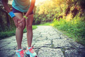 Woman runner hold her sports injured knee. Athlete, female.