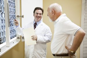 Doctor or chiropractor explaining the results of a CT scan of the spine to his patient suffering with low back pain.
