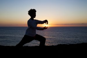 young woman performs tai chi moves silhouetted agains sunset