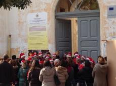 i bambini recitano delle poesie davanti all'ingresso della loro scuola