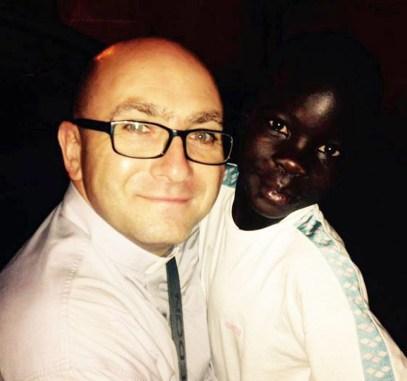"""PURE IL BASKET DA UNA MANO Don Giuseppe Venneri con un piccolo ospite. Il 19 dicembre sarà inaugurata in Uganda una casa di accoglienza, realizzata grazie anche al contributo della """"Andrea Pasca"""" di basket"""