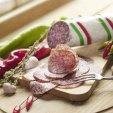 PICK original ungarische Salami angeschnitten auf Holzbrett mit Gewürzen und Paprika