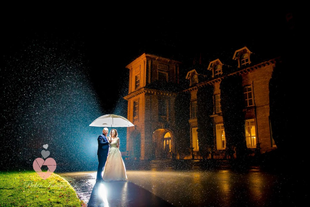 Bride and groom in the rain, rain all light up it camera flash at night, Eastwood Park.