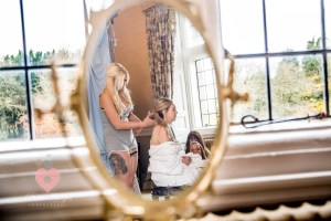 The bride in the mirror, hair being done by a sister at Clearwell Castle.
