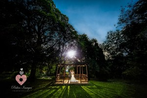 The Royal George at birdlip wedding . bride and grooming the pergola at sunset