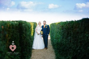 Bride and groom posed in-between hedges in autumn Pickin Images Photography
