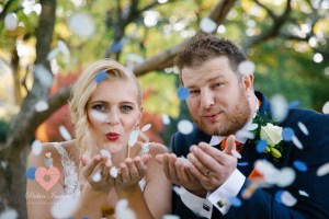 Bride and groom blowing confetti in autumn Pickin Images Photography