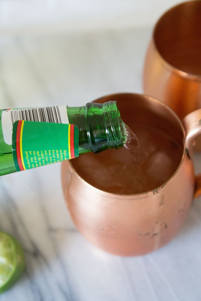 ginger beer pouring into a copper mug