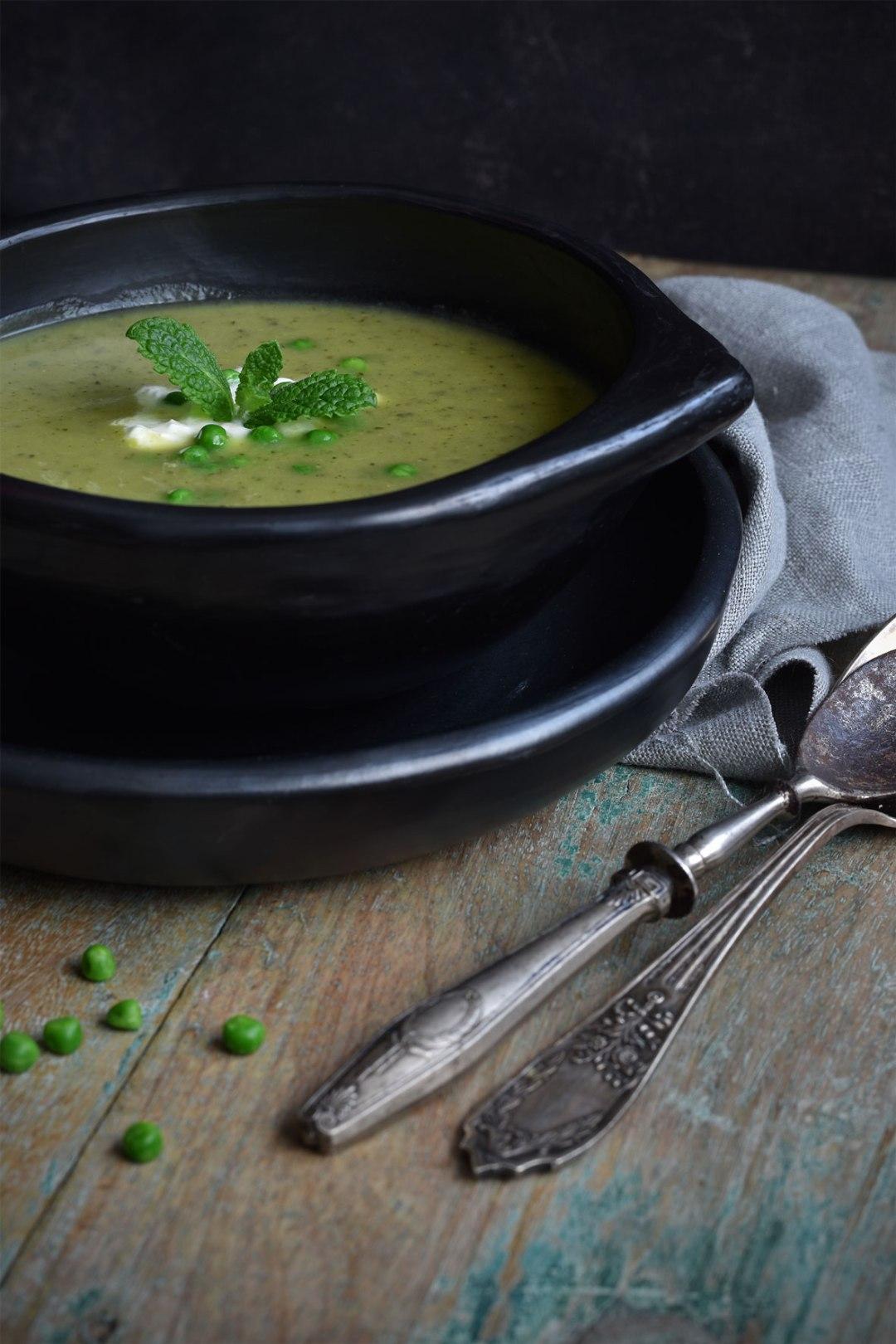 Een frisgroene courgettesoep met doperwten, munt en zure room die de lente in huis haalt.