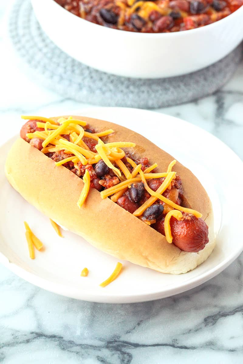 Chili dog on a white plate with shredded cheese on top
