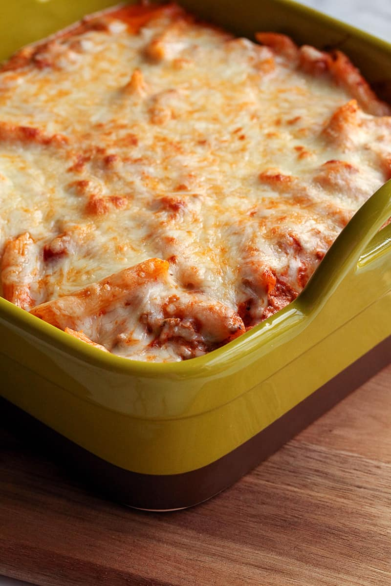 Green casserole dish with creamy baked ziti and melty cheese on top sitting on a wooden cutting board