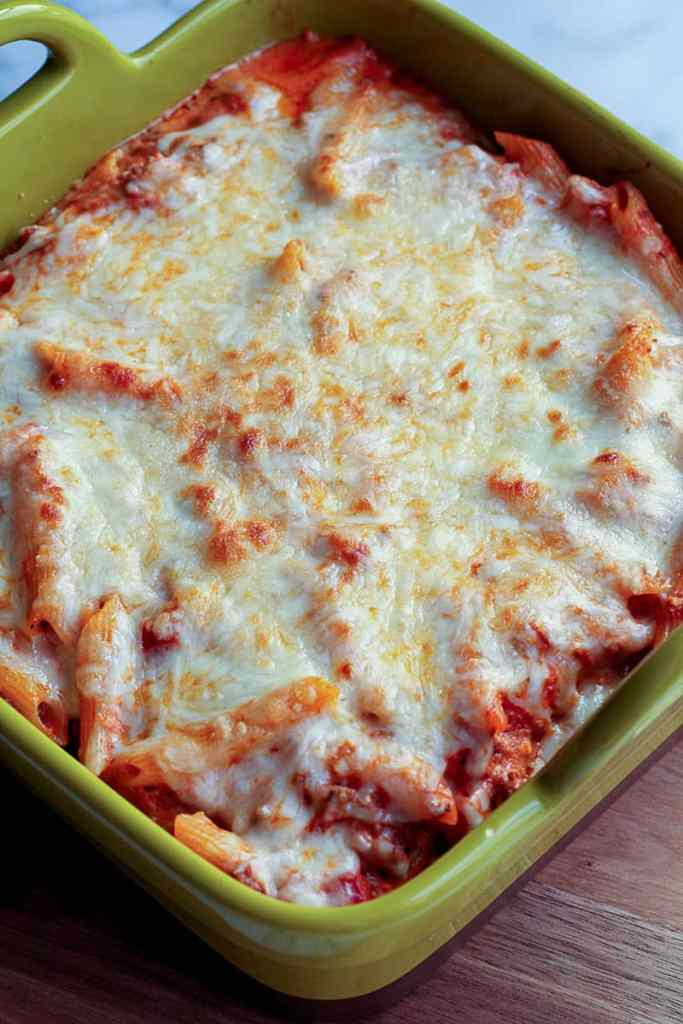 Casserole dish with creamy baked ziti and melted mozzarella cheese on top