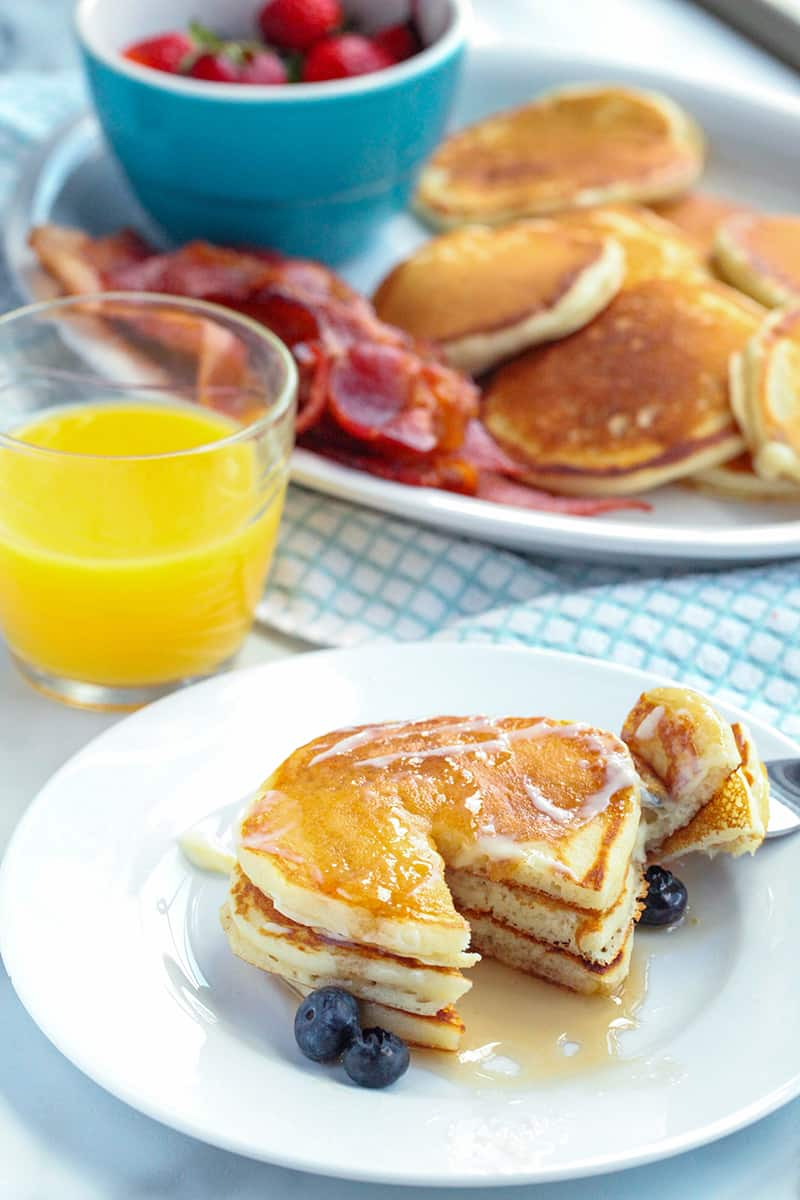 Plate with pancakes and a glass of orange juice in background with platter with bacon and pancakes in the background
