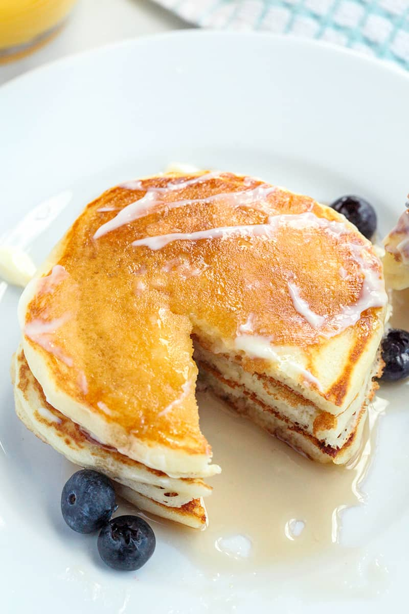 A stack of pancakes on a white plate with syrup and blueberries