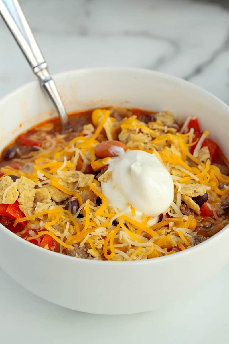 bowl of soup with sour cream and shredded cheese