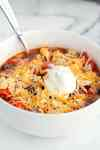 White bowl with slow cooker taco soup topped with sour cream and shredded cheese