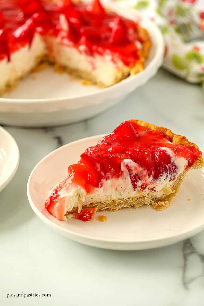 A slice of strawberry cream pie on a white plate