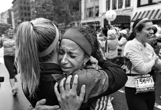 An emotional Elise Wulff, at right, is comforted by Erin Roy at the Boston Marathon finish line after the two finished the Boston Strong OneRun today, May 25, 2013, in remembrance of those who didn't or couldn't finish April 15. Wulff ran her first marathon April 15th, in hopes of raising money for Voices of Hope, but could not finish due to the bombings.