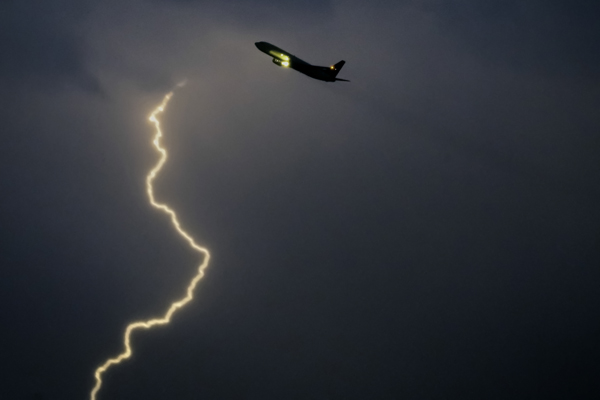 June 24, 2013. A distant lightning bolt strikes well behind a departing Logan airliner.