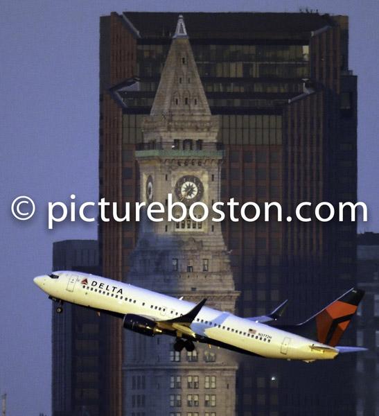 October 19, 2013 Boston's Custom House frames a departing jet.