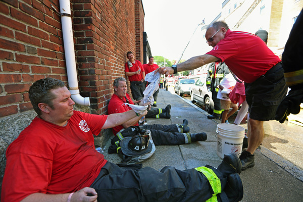 08/07/2015-Boston,MA. Boston firefighters from the Dudley Square fire house receive cold towels from Paul Boudreau, of the Boston Sparks Canteen Crew, during a 3 alarm fire at 6 Waverly St. in Roxbury today. Staff photo by Mark Garfinkel