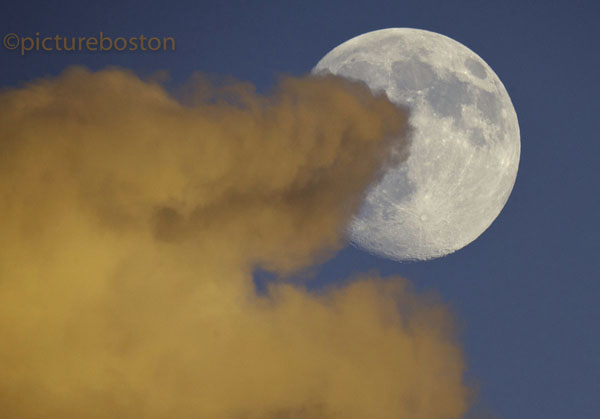 August 27, 2015. An almost-full Boston moon emerges from behind a colorful cloud at sunset.