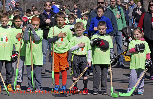 04/09/2016-Boston,MA. Area children children salute the flag during the National Anthem, shortly before they competed at the annual Shamrock Shootout Street Hockey Tournament on Temple St. in the West Roxbury section of the city, Saturday morning. Staff photo by Mark Garfinkel