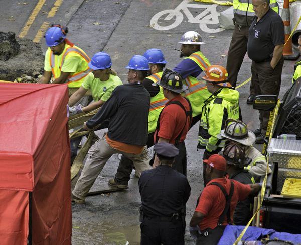 October 21, 2016-Boston,MA. Firefighters and workers scurry into position in the first moments after a trench collapse and water leak killed at least one worker and injured another Friday afternoon on Dartmouth street.. Staff photo by Mark Garfinkel