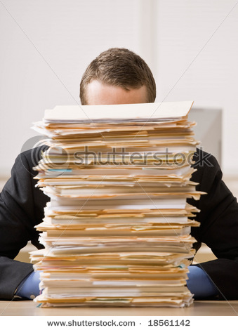 Overworked frustrated worker looking at pile of file