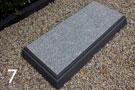 Tumši pelēka betona kapu apmale ar graudiņiem, slēgta