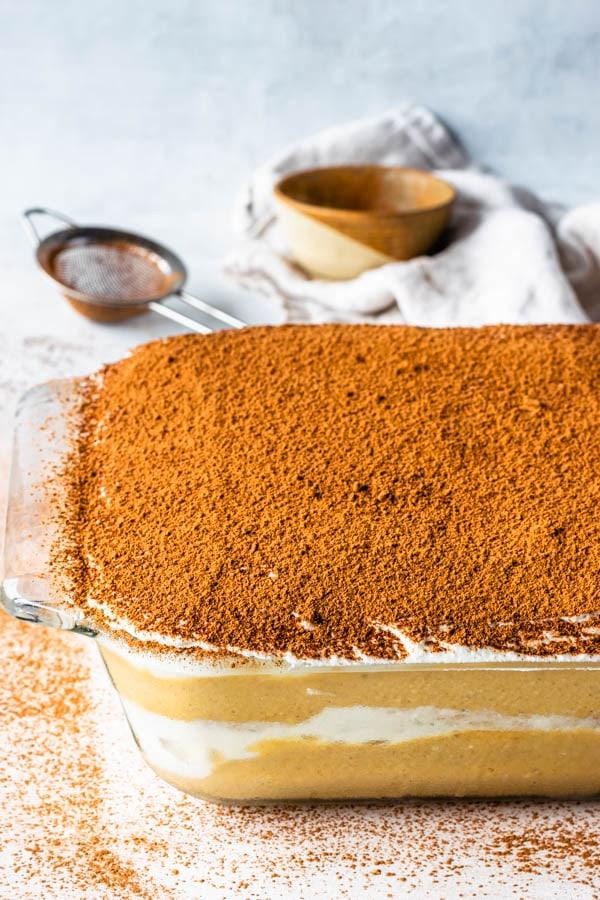 Pumpkin tiramisu dusted with cocoa powder in a glass dish