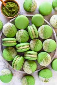 Matcha Macarons dipped in white chocolate topped with matcha powder.