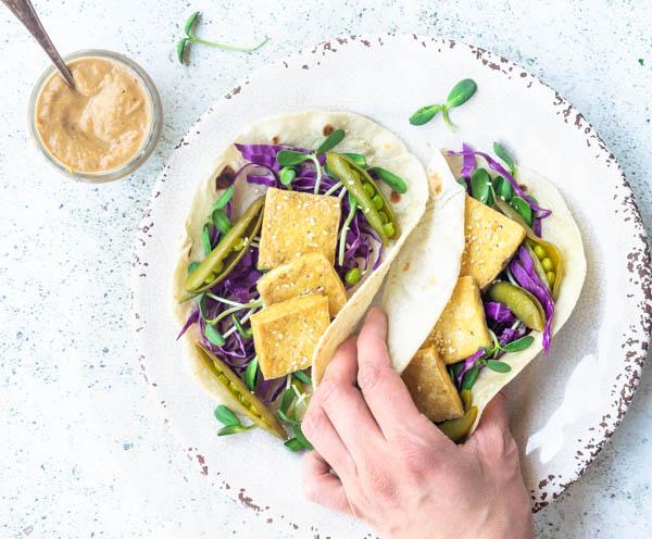 vegan tofu tacos with peanut sauce, hand grabbing taco
