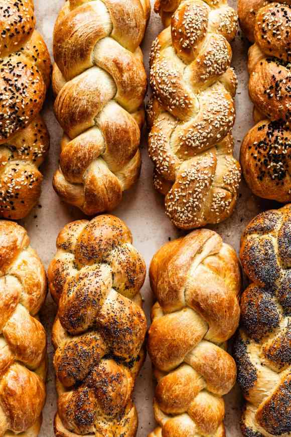 8 loaves of challah bread, some topped with sesame seeds, some plain and some topped with poppy seeds.