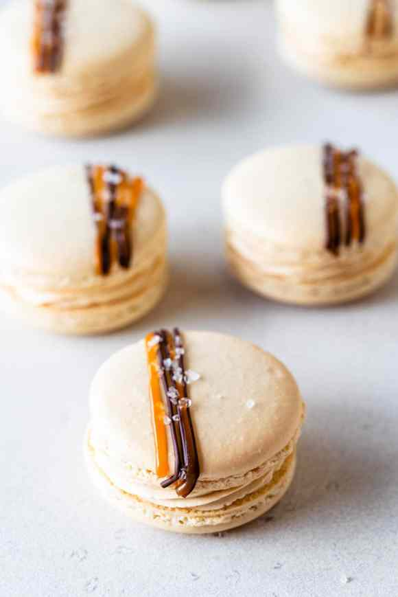 Salted Caramel Macarons filled with buttercream topped with a drizzle of caramel and chocolate and flaky sea salt
