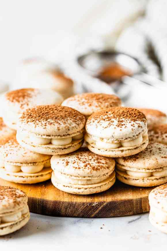 Tiramisu macaron filled with mascarpone frosting, dusted with cocoa powder on top of a wooden board