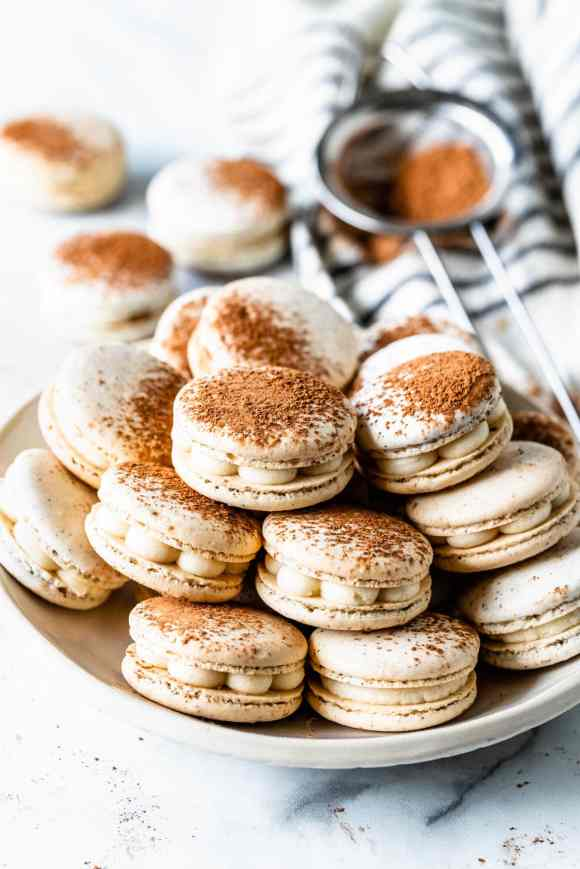 Tiramisu macaron filled with mascarpone frosting, dusted with cocoa powder in a plate