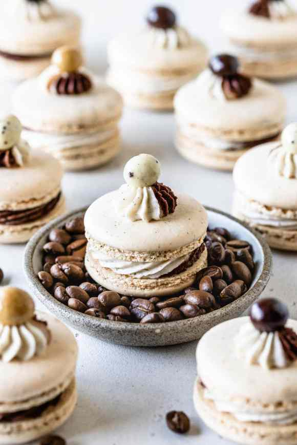 coffee macaron on top of a bowl full of coffee beans, more coffee macarons around it, all macarons have a chocolate covered espresso bean on top.