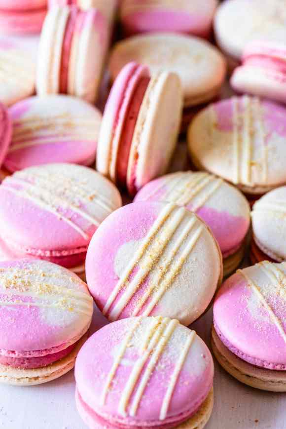 Strawberry macarons with two color shells drizzled with white chocolate and topped with graham cracker crumb.