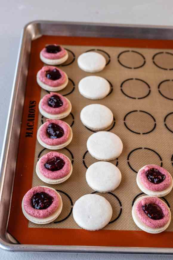 white macarons filled with a ring of pink frosting around the edges, and a center of raspberry jam.