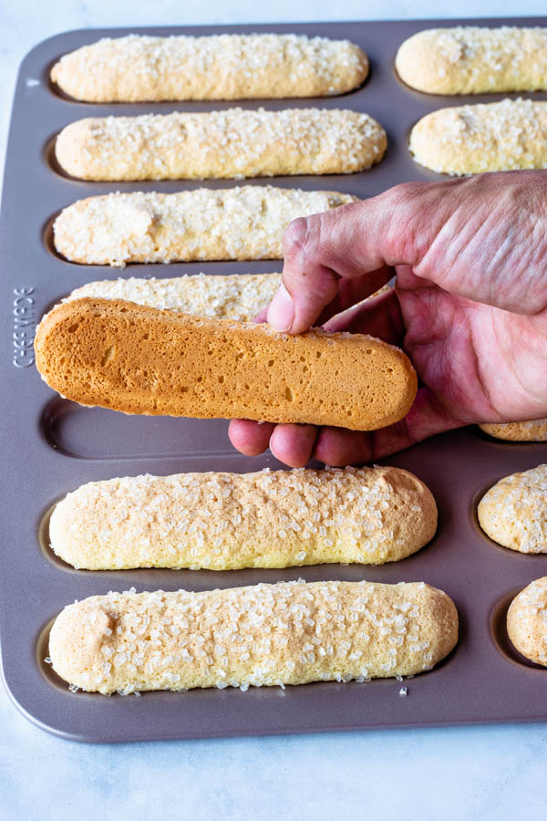 lifting a ladyfinger cookie off the pan to show the bottom