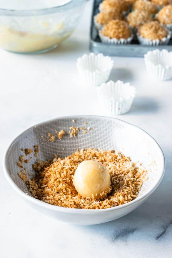 rolling coconut fudge ball into coconut flakes