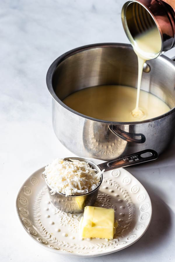 ingredients to make coconut fudge: coconut flakes, butter, and condensed milk