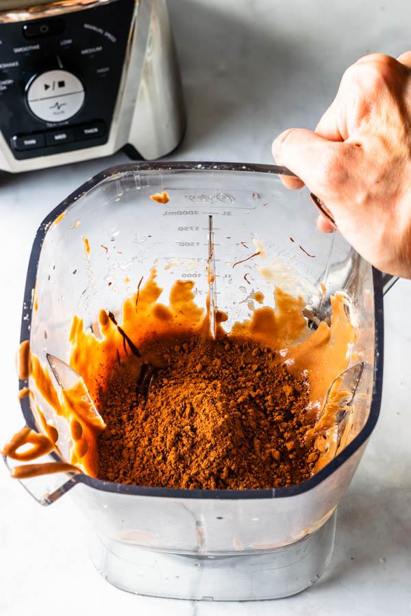 adding hazelnut butter to blender to make vegan hazelnut cheesecake
