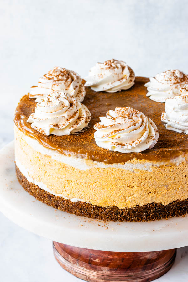 vegan pumpkin cheesecake with caramel sauce on top and whipped coconut cream and a sprinkle of pumpkin spice