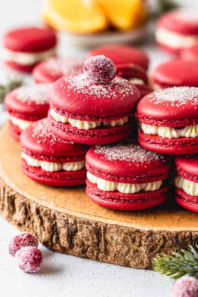 cranberry macarons with dusting of sugar on top, on top of a wooden board topped with sugared cranberry.