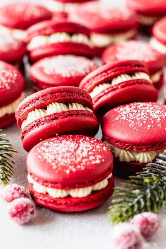 red macarons stacked, filled with cranberry sauce and orange buttercream.